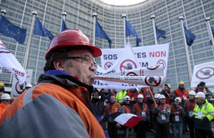 A steelworkers blows a paper horn during a demonstration of steelworkers in the European quarter of Brussels on Monday, Feb. 15, 2016. Thousands of steel workers from across the European Union demonstrated against the import of cheap Chinese products and warned EU leaders not to acerbate the situation by granting Beijing market economy status. (AP Photo/Virginia Mayo)